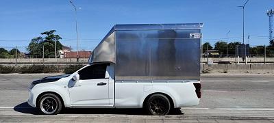 รถกระบะขนส่งบรรทุกของติดตู้จอดอยู่รอรับพัสดุ