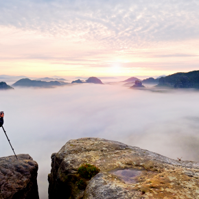 Professional nature photographer over clouds. Man takes photos with camera on tripod on rocky peak.